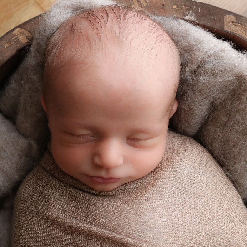 gorgeous sleeping baby boy, wrapped up lying in a bowl wearing brown