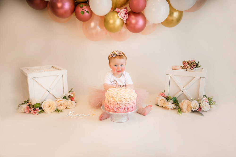 bright eyed baby girl wearing a pink headband and matching tutu for her cake smash session in hampshire