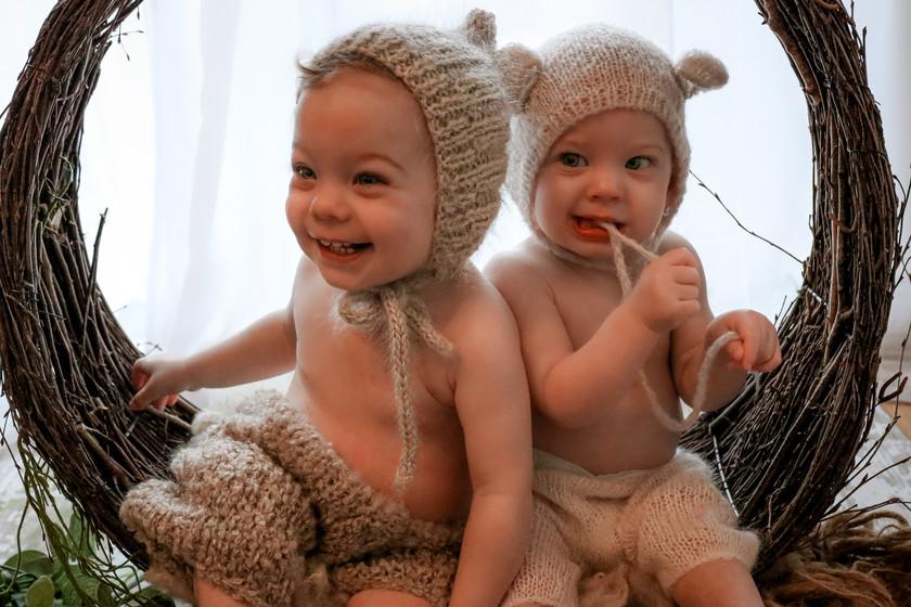 twin boys sitting in wicker chair smiling
