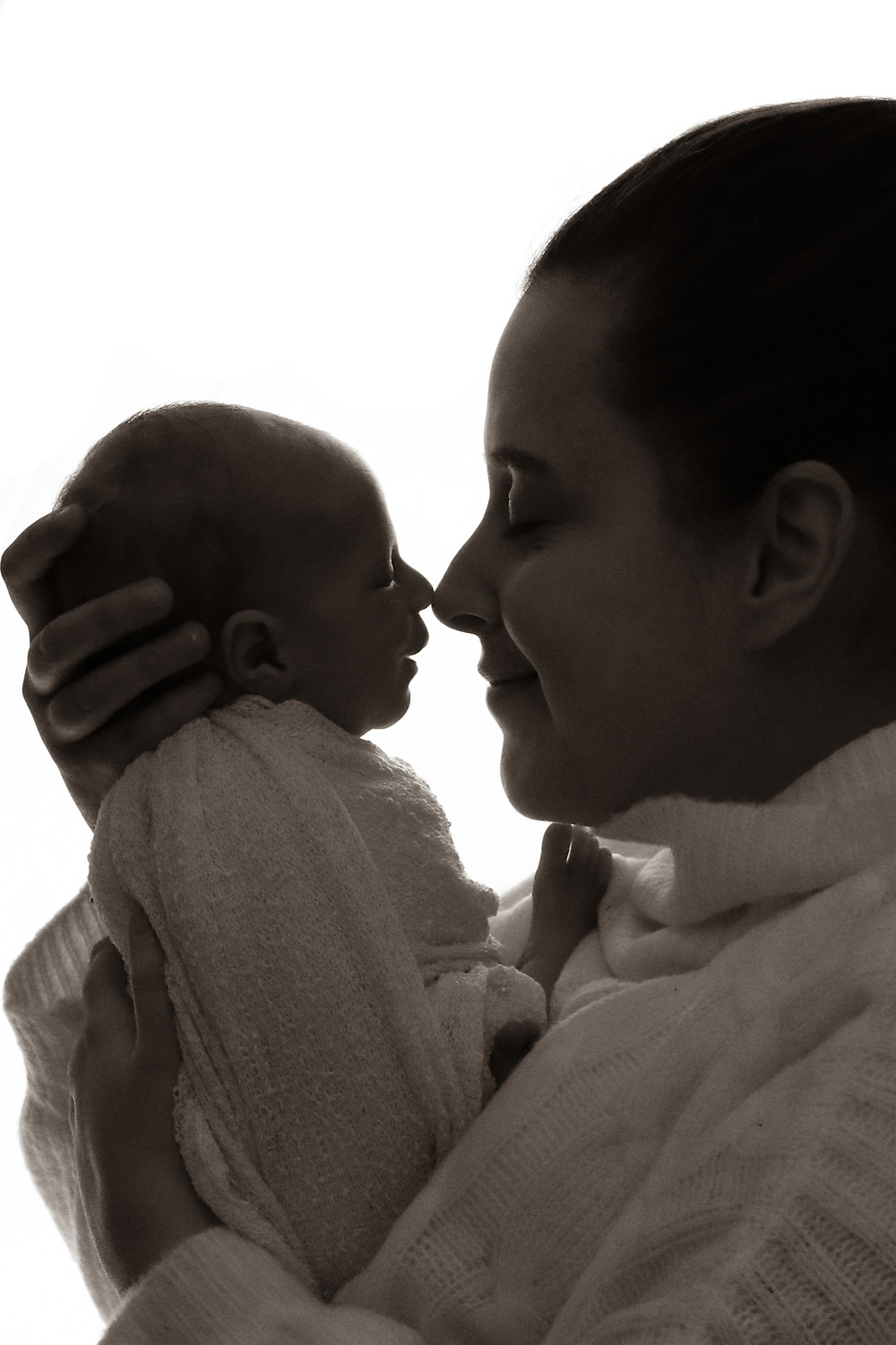 silhouetted shot of woman holding newborns nose up to her nose