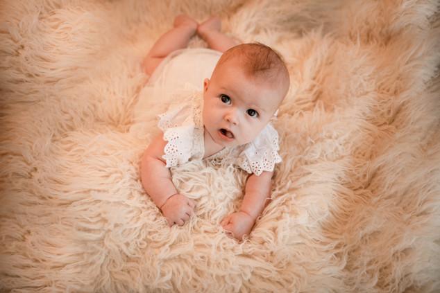 baby girl lying on a white furry rug