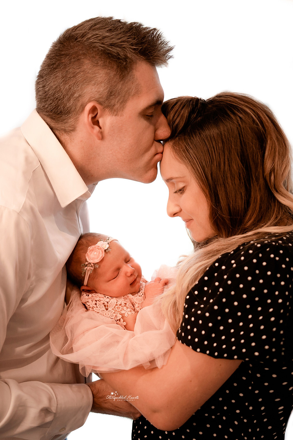 newborn held by her mum and dad looking over her