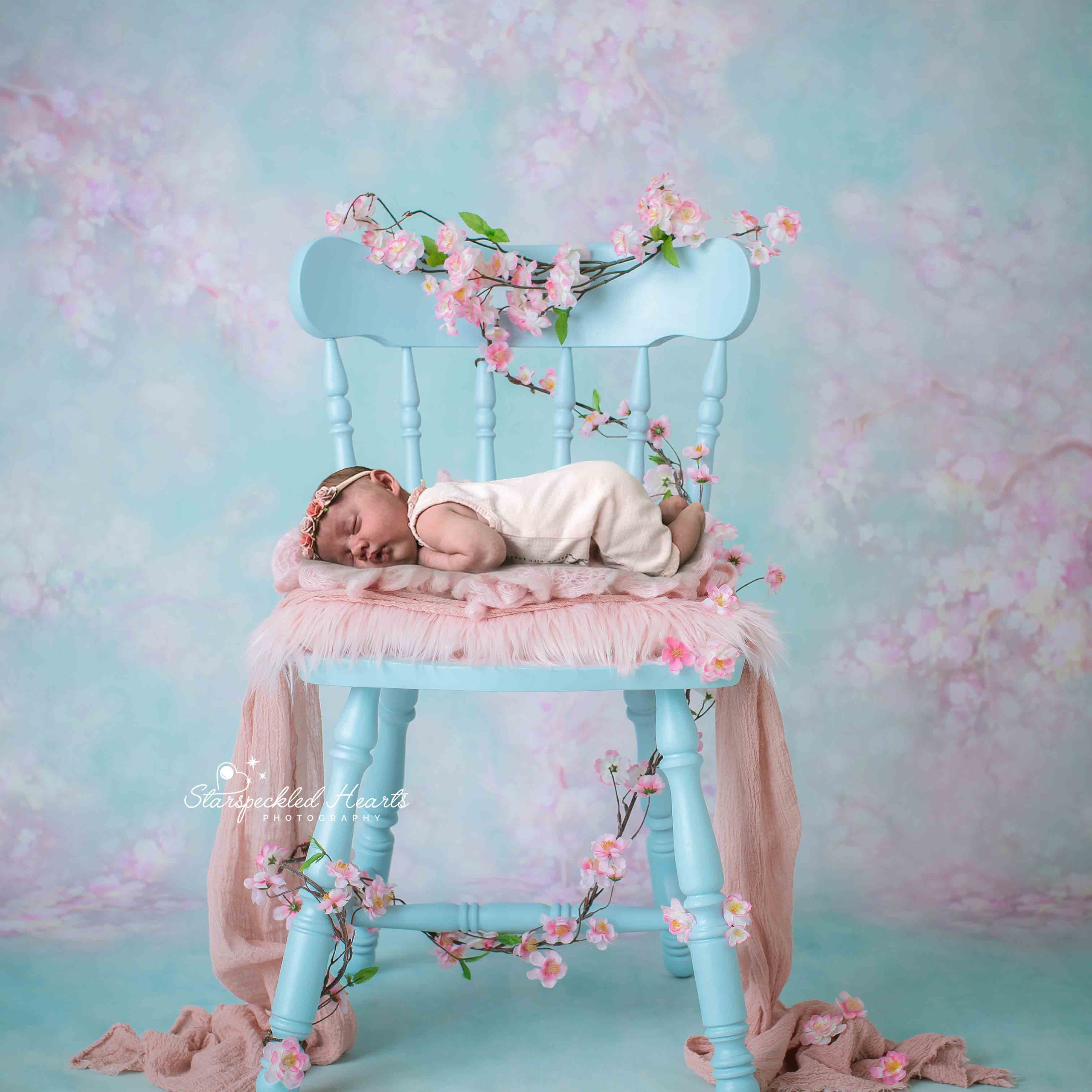 sleeping baby girl laying on a blue chair surrounded by pink flowers