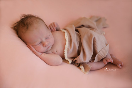 adorable sleeping newborn lying on her tummy on a pink background with a pink wrap around her