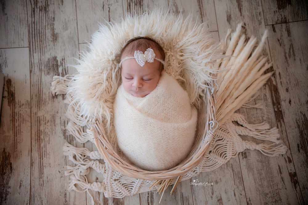 sleeping baby girl in a white swaddle, lying in a white basket
