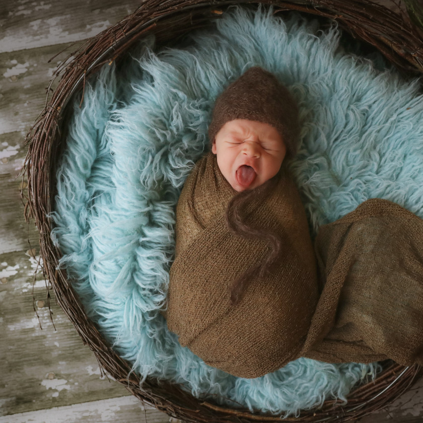 gorgeous sleeping baby boy laying on a turquoise flokati rug, wearing a brown bonnet with a turquoise trim and a matching brown wrap