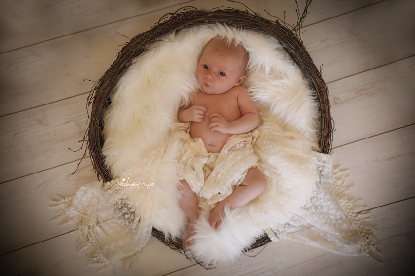 gorgeous baby girl covered in a lacy wrap, lying in a white wicker basket