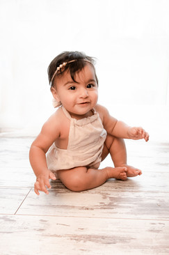 baby girl with black hair in a cream romper sitting on a wooden floor smiling