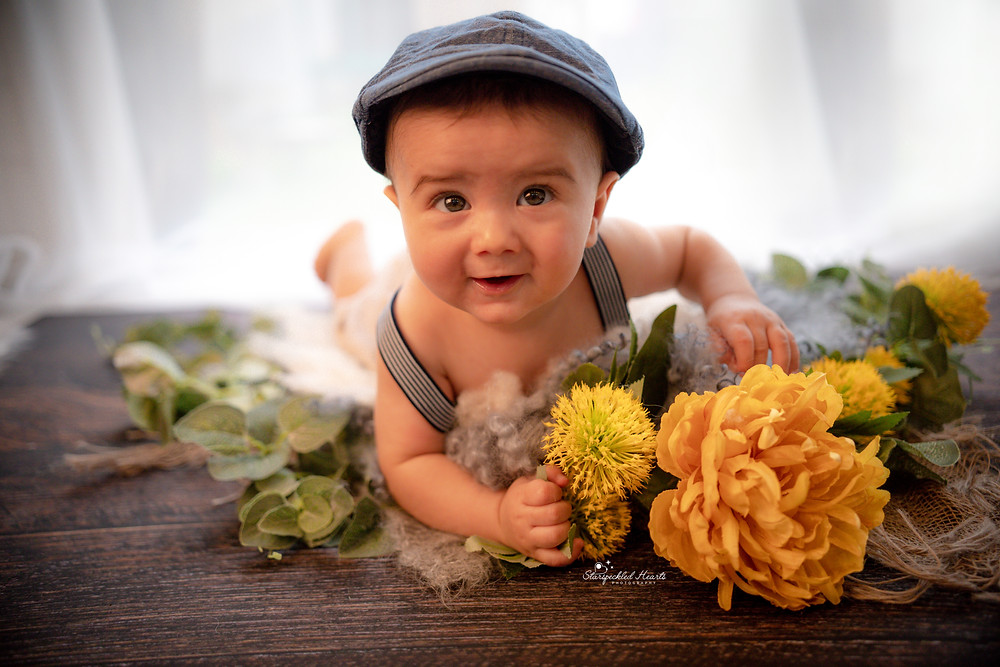baby boy lying on his tummy wearing braces and a flat cap, surrounded by yellow flowers and greenery