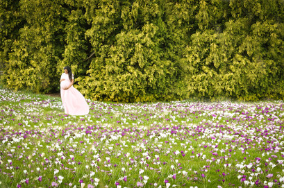 beautiful pregnant woman with long black hair wearing pink flowy dress, standing in a green grassy field of white and purple flowers in front of a large group of trees in rhs wisley botanical gardens