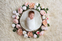gorgeous baby girl lying in a bowl surrounded by pink roses