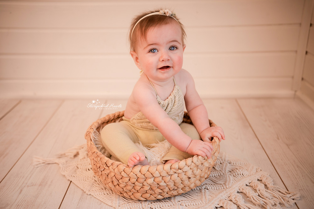 smiling baby girl wearing a lacy romper sitting in a woven basket on top of a macrame rug