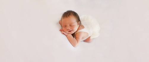 beautiful baby girl laying on a white background in a white frilly romper