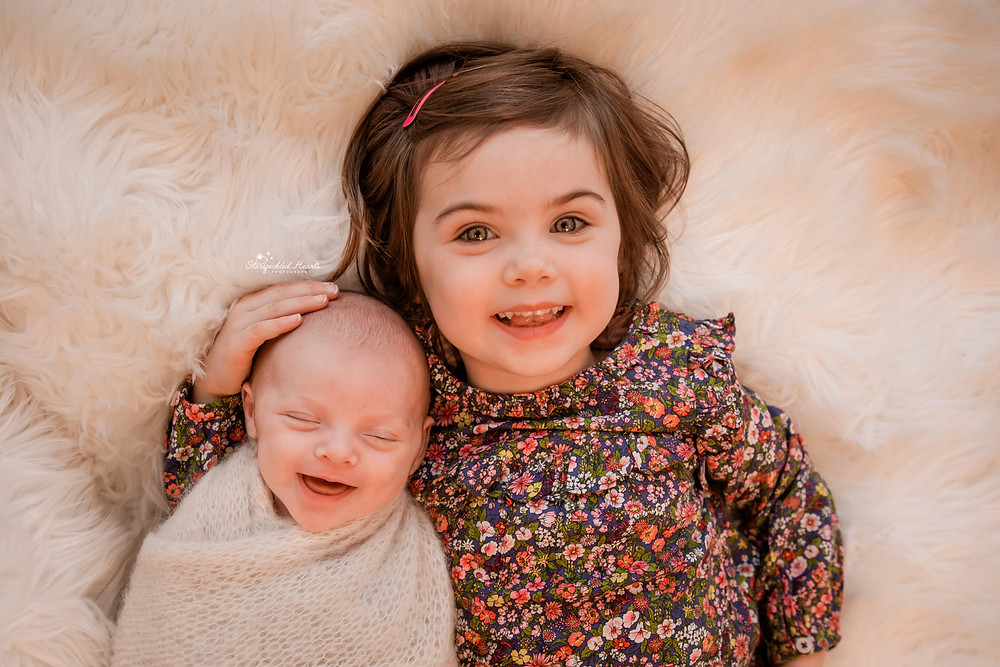 big sister holding her little brother gently whilst both smiling at their newborn photography session in hampshire