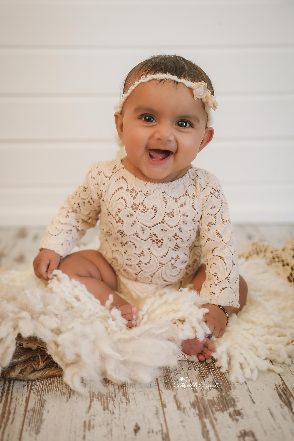 gorgeous baby girl with a big smile on her face wearing a white lacy romper