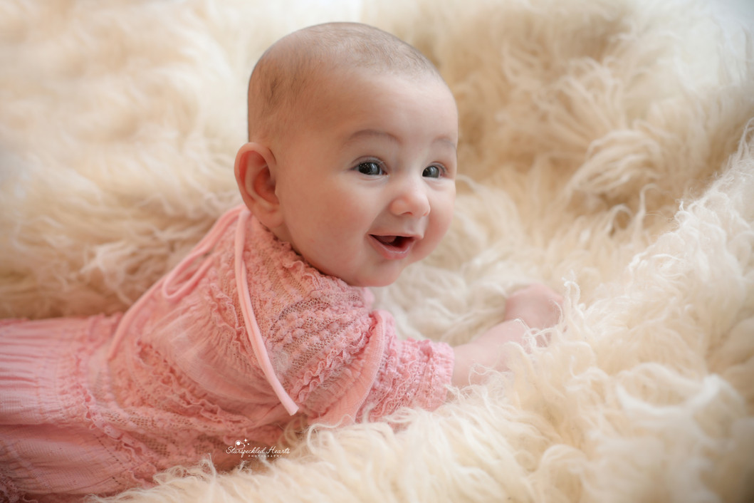 smiling baby girl wearing a pink lacy romper, lying on a white fluffy rug