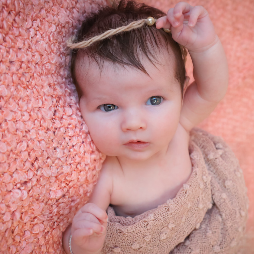 blue eyed newborn in pink with arms over head