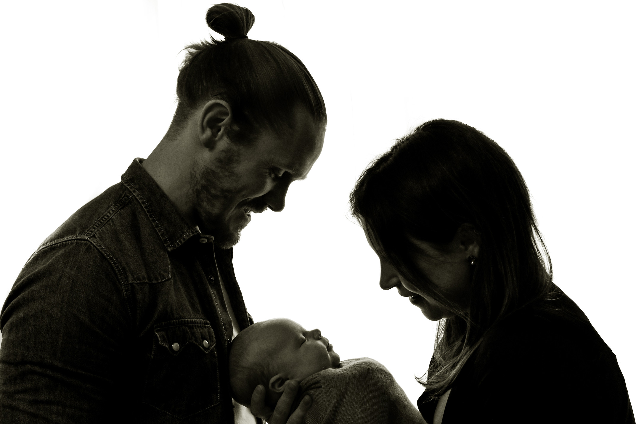 black and white photo of man and woman gazing down at their newborn