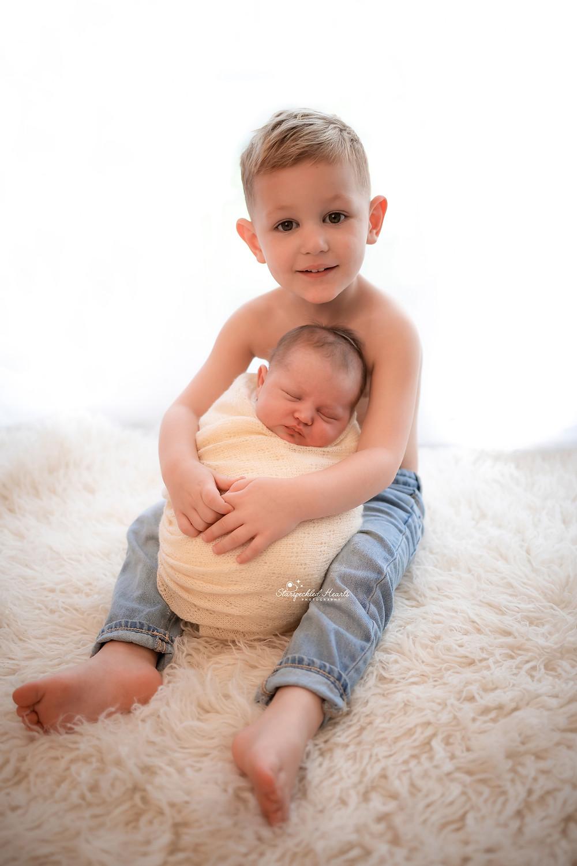 adorable baby boy cuddling his newborn baby sister