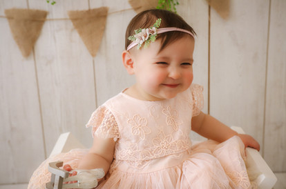 smiling little girl wearing a pale pink lace embroidered dress and matching headband