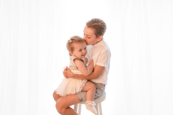 a brother with his baby sister sitting together on a wooden stool, having a cuddle