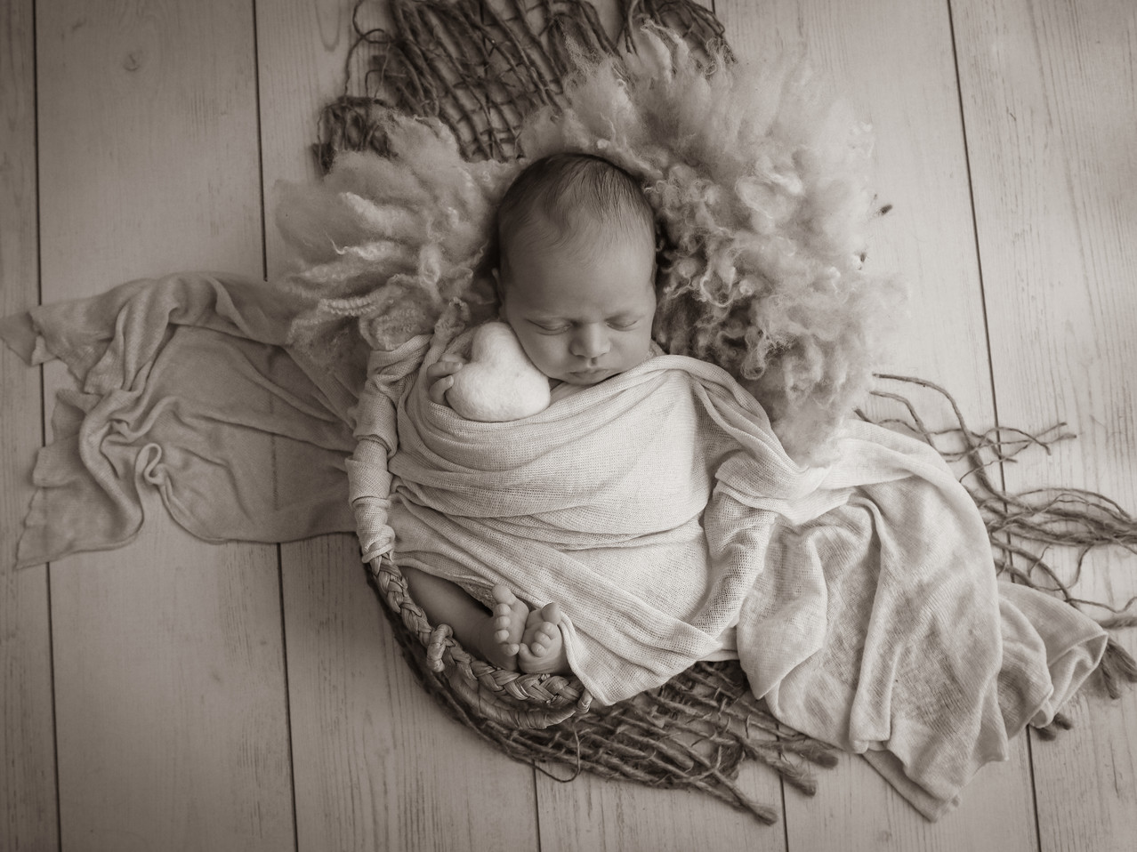 sweet newborn boy sleeping, lying in a wicker basket with a textured white wrap over him, in black and white