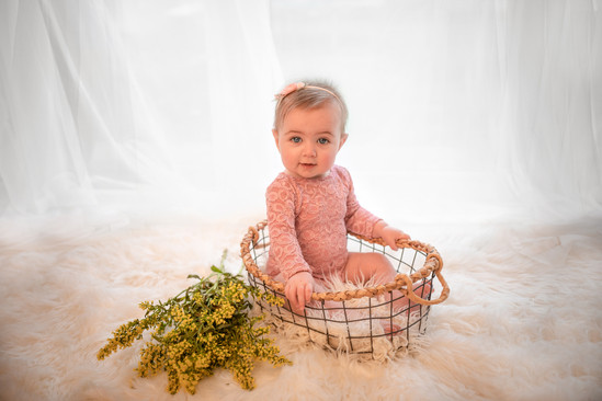 baby girl siting in a little basket with beautiful yellow flowers surrounding it, wearing a pink lacy romper and matching headband for her little sitter photography session