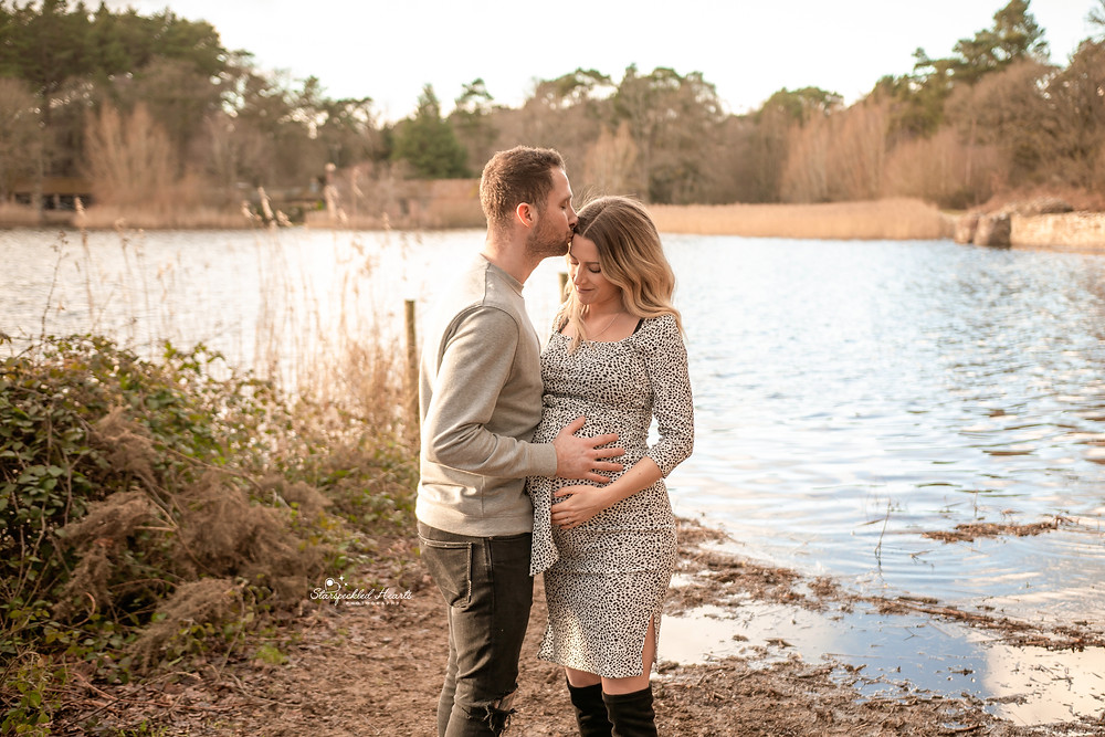 bump to baby maternity pregnancy photoshoot outdoors near a large lake, a pregnant woman and her husband embracing