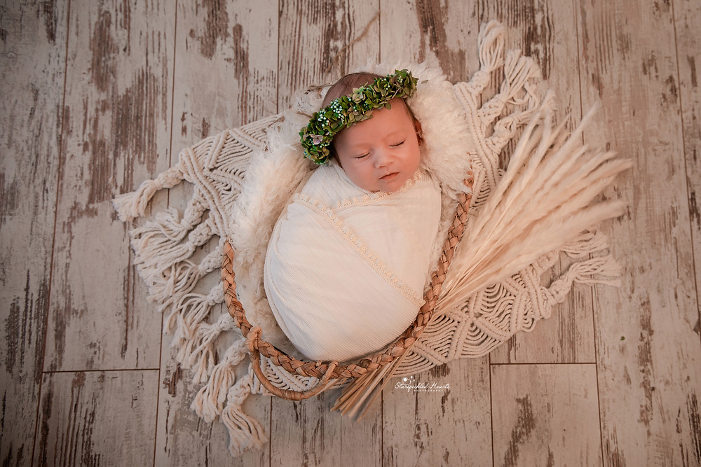 beautiful sleeping newborn baby girl wearing a leafy wreath on her head, wrapped in white and lying in a wicker basket