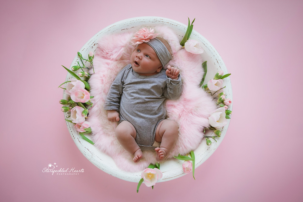 baby girl lying in a white bowl stuffed with a pink fur blanket, surrounded by pink flowers and green leaves