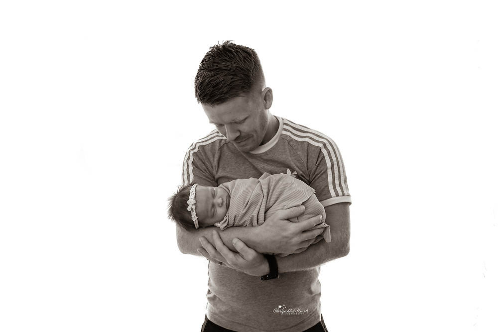 a man cradling his newborn baby girl