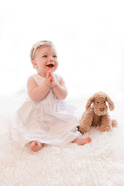 smiling baby girl wearing a white dress sitting on a white fluffy rug with her teddy at her baby photography session with starspeckled hearts photography