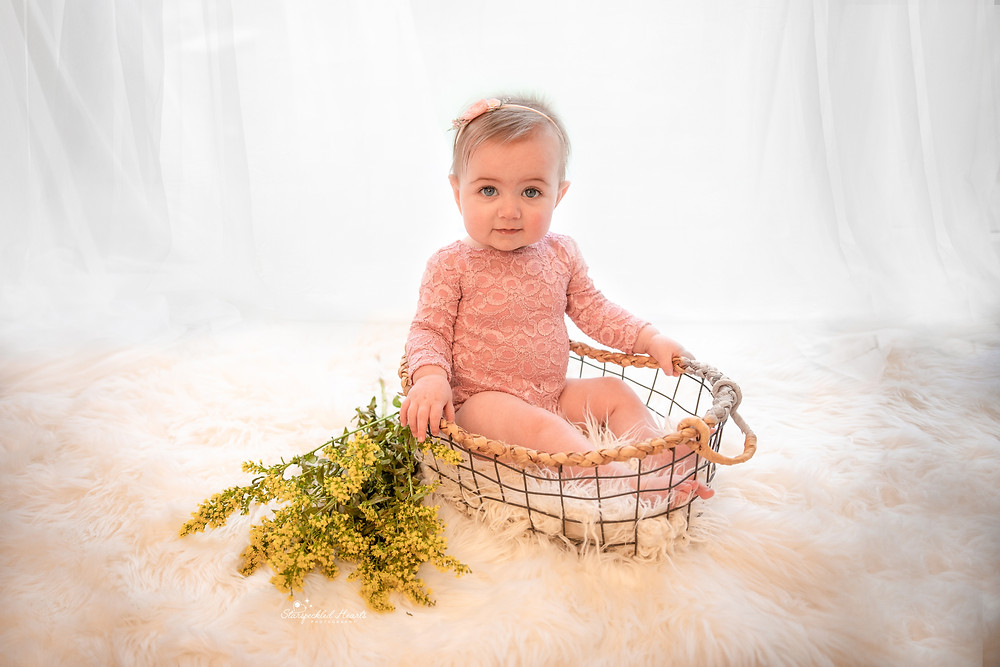 beautiful baby girl in a mesh basket surrounded by small yellow flowers for her baby photography session with starspeckled hearts photography