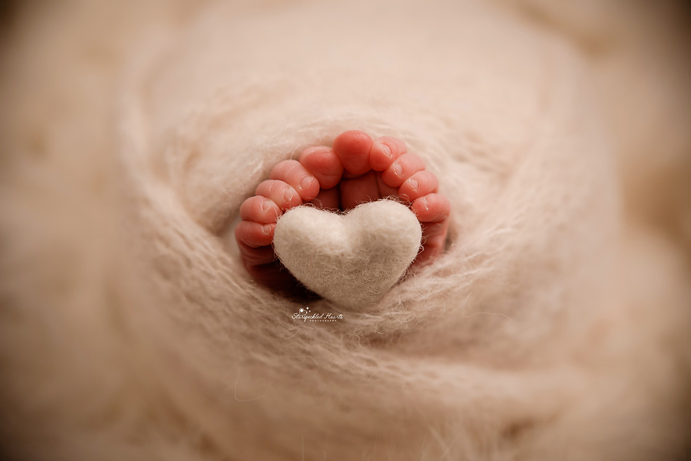 close up of little newborn toes curled around a white felt heart in berkshire
