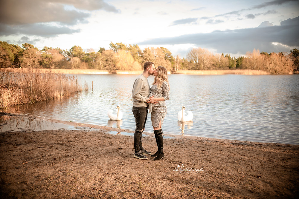 beautiful pregnant mum and her husband kissing, standing near a large lake with swans in the background for their maternity session in hampshire with starspeckled hearts photography