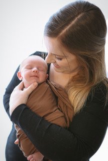 woman with long brown hair cradling her smiling newborn baby boy in her arms