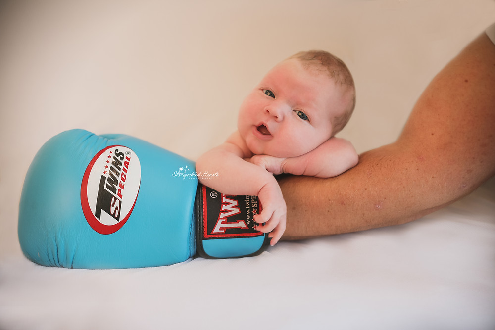 smiling baby girl lying on a blue boxing glove on her fathers arm