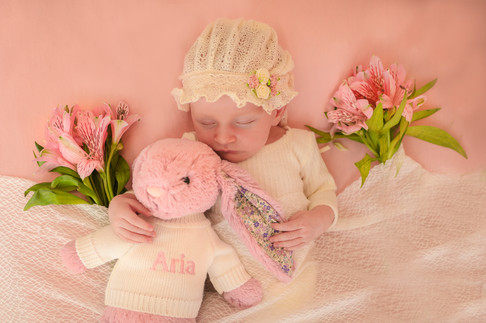 """adorable baby girl wearing a lace bonnet, laying down on a pink blanket surrounded by flowers on either side of her, cuddling a pink teddy with the name """"Aria"""" on it"""