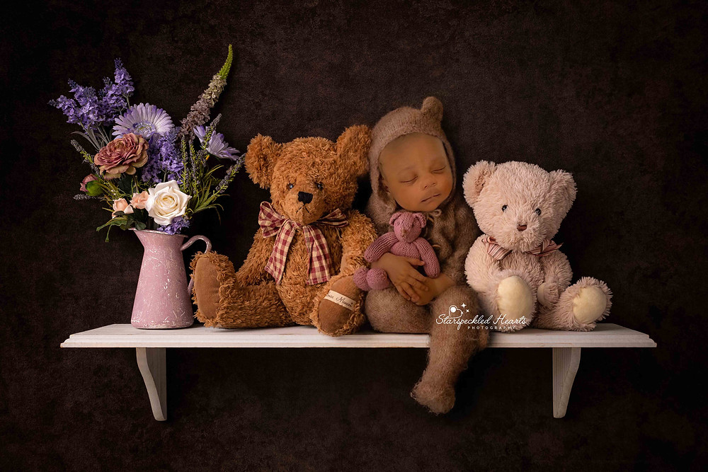 sleepy baby boy in a brown bear romper, sitting on a shelf with two smaller teddies