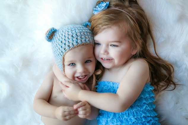 gorgeous girl with brown hair and blue eyes, wearing a blue frilly romper and a blue flower headband cuddling a little boy wearing a blue knitted bear bonnet with ears, both smiling