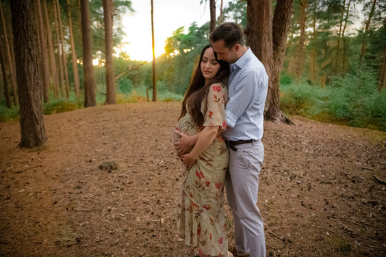 man and woman kissing standing in a forest with the sun setting behind them for their outdoor maternity session with starspeckled hearts photography