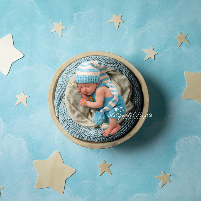 sleeping newborn lying in basket surrounded by gold stars on blue background