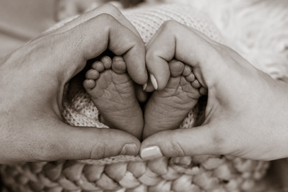 newborn feet with both parents' hands making a heart shape around them in black and white