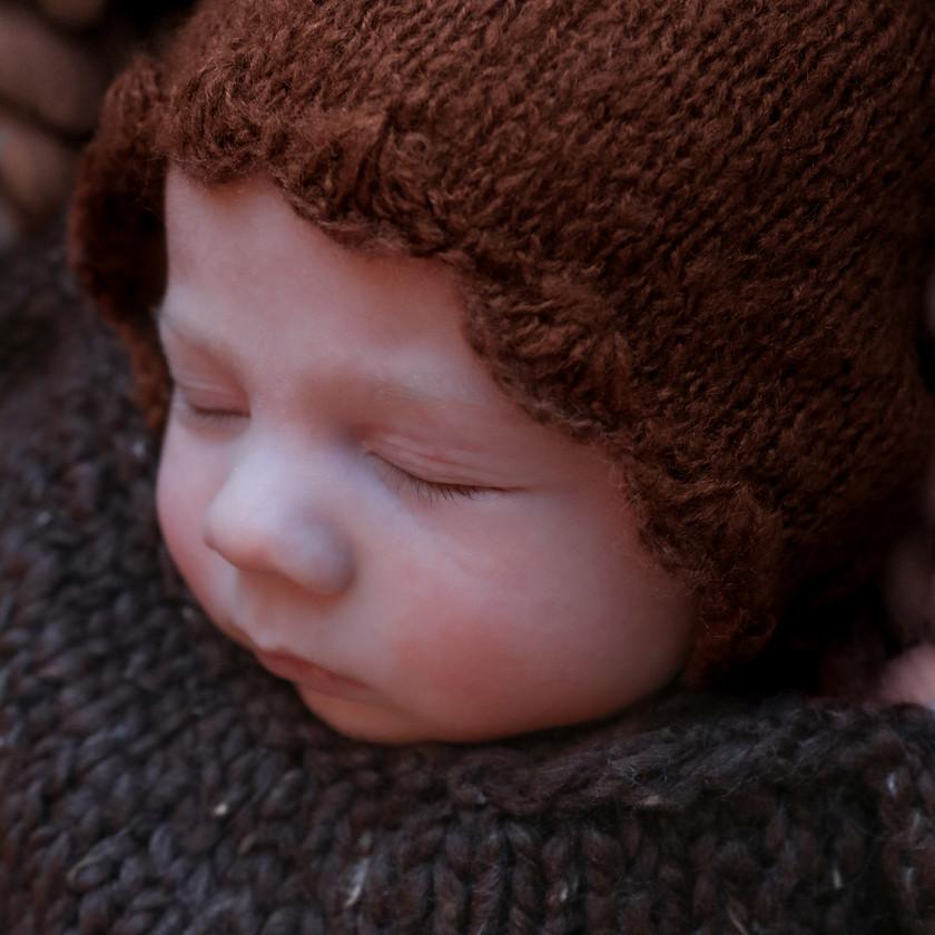 closeup of sleeping newborn wearing brown scalloped bonnet