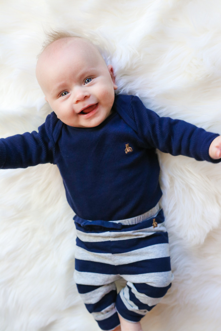 smiling baby boy lying on white rug wearing navy outfit