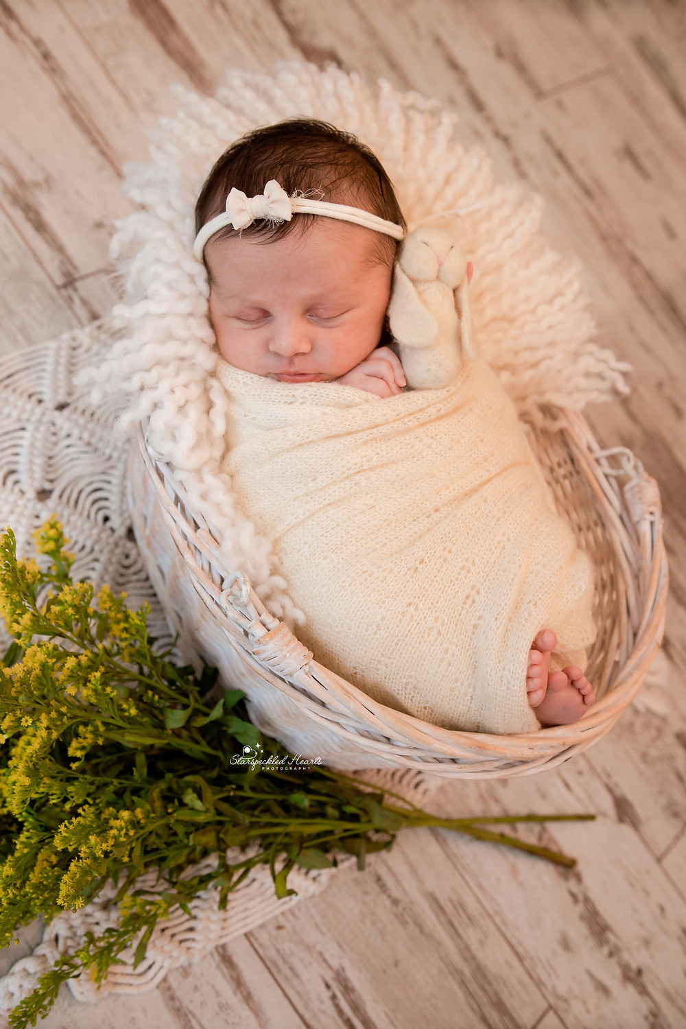 sleeping newborn baby girl lying in a wicker basket surrounded by yellow flowers
