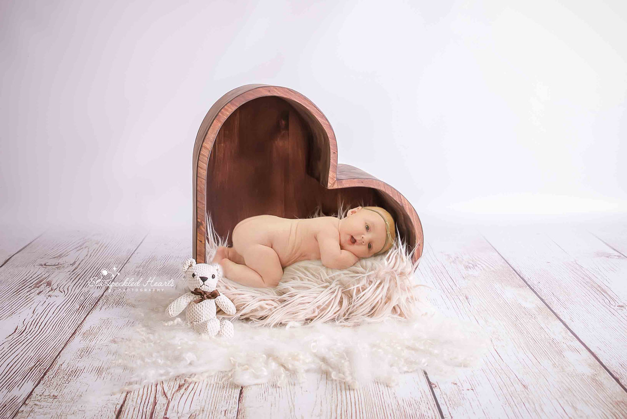 adorable baby girl laying on her tummy inside a brown wooden heart