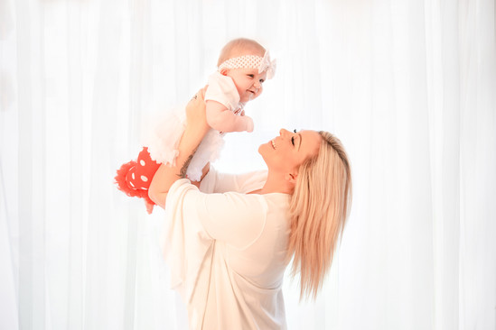 mother and daughter portrait, of mum holding baby up over her head, both smiling
