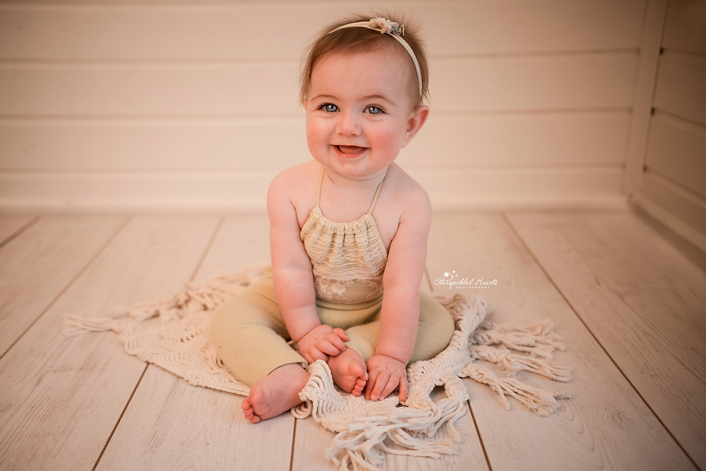 gorgeous baby girl smiling sitting on a macrame rug