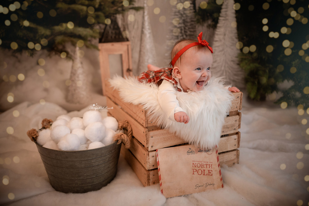 christmas mini session in hampshire, cute baby girl lying in a wooden crate with a big smile on her face